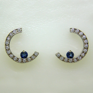 Classic, elegant, and contemporary Sapphire and Diamond earrings in a crescent moon shape. Crafted in  14 karat White Gold set with beautiful 4mm cornflower blue Sapphires, accented by .28ct. T.W. of Ideal cut Diamonds, on posts. Each earring measures 1/2 inch long.  Designed, and created in our studio by the artist Stuart J.