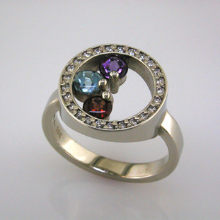 A Mother's ring for now. Elegant, and classy, you will be proud to wear this family birthstone every day. This diamond and birthstone Mother's ring is priced in 14k gold, and can be made in any karat or color of gold, and in platinum. It is individually crafted to be Perfectly You, and takes about 2 weeks to create.  Call us for more information about how we can customize this design Just For You.   Designed, and created in our studio by the artist Stuart J.
