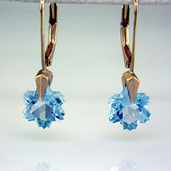 What's better than one sparkling snowflake? Two, of course. One for each ear. And you can turn up the heat, because these snowflakes won't melt. Exclusively ours, each blue topaz snowflake is custom cut just for us, in Canada, by master gem cutters. Each snowflake measures 8mm, and dangles in a 14 karat white gold Piercette® setting on a lever back, measuring 1 inch long. Designed and handmade by the artist Stuart J.  A Piercette® is a patented method of setting, with a gemstone that moves. The gem is set so that it swivels with every movement of the wearer, exhibiting extra sparkle.