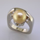 This one-of-a-kind Tahitian Pearl ring is truly a masterpiece. Modern, and elegant, this 14 karat white gold ring gently holds a spectacular 9.7mm golden colored Tahitian Pearl, framed by 2 round Ideal cut Diamonds totaling .20ct. Finger size 6. We can size it up or down about 1.5 sizes, or it can be special ordered in your finger size. Measures 3/4 inch wide.  Designed, and created in our studio by the artist Stuart J.