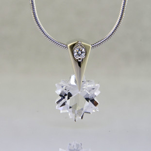 The hottest snowflake around! Custom cut, exclusively for us, in Canada. Dangling from a 14 karat white gold Piercette® pendant, with a perfectly cut sparkling 8mm Colorless Topaz snowflake cut gemstone, and accented with a single .03ct. Ideal cut Diamond. Includes a 14k white gold 1mm diameter, smooth snake chain, 16 inches long. Measures 1/2 inch long.  Designed and handmade by the artist Stuart J.  A Piercette® is a patented method of setting, with a gemstone that moves. The gem is set so that it swivels with every movement of the wearer, exhibiting extra sparkle.