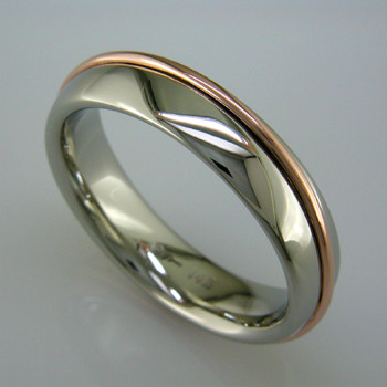 Just a little twist on the simple comfort fit man's wedding ring, this 6mm wide, 14 karat White Gold ring is wrapped in a 14 karat Rose Gold wire. Comfort fit to feel great when you are wearing it.  This wedding ring is priced in 14k gold, and can be made in any karat or color of gold, and in platinum. Please allow us 2 weeks to make it. It will be worth it!  Designed, and created in our studio by the artist Stuart J.