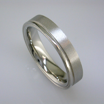 Sleek man's wedding band, 5mm wide, comfort fit, in 14 karat White Gold with a soft matte finish and a shiny edge. For the sophisticated man.  This is a special order item; please call with finger size, and allow two weeks for us to make it. It will be worth it!  Designed, and created in our studio by the artist Stuart J.
