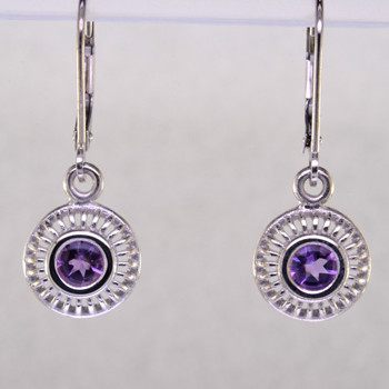"""Blending traditional and modern, these earrings dazzle for day or night. Hand crafted in 14 karat white gold with sparkling 4mm Amethyst buff top gemstones dangling on lever backs. Earrings measure 1"""" long.    Designed, and created in our studio by the artist Stuart J."""