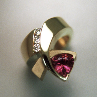 Beautiful, modern and fun. So unique, everyone will admire it. Made in 14 karat yellow gold with a sparkling 7.5mm Rhodolite Garnet Trillion gemstone, and .09ct. T.W. of ideal cut diamonds. Finger size 6.5.   Call us for more information about how we can customize this design Just For You. Designed, and created in our studio by the artist Stuart J.