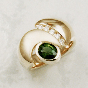 You will be so stylish in this one of a kind gemstone ring, crafted in 14 karat yellow gold, with a dreamy deep green .98ct. oval Chrome Tourmaline, accented with .15ct .T.W. ideal cut diamonds. Beautifully finished with a contrasting satin treatment, for a sophistcated look. Finger size 6. Designed, and created in our studio by the artist Stuart J.
