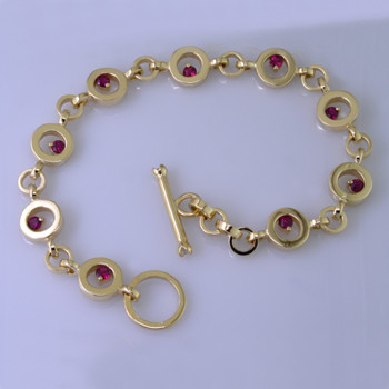 You will love this modern, fun circle bracelet, in 14 karat yellow gold, with nine 3mm round Fine Ruby Gemstones.  The custom designed toggle clasp has 2 round ideal cut diamond accents. Measures 7 3/4 inches long. Designed, and created in our studio by the artist Stuart J.
