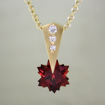 "This Garnet snowflake and Diamond Piercette® pendant will melt your heart. Dangling in 14 karat yellow gold, with an 8mm custom cut deep red Garnet snowflake and sprinkled with .07ct. T.W. Ideal cut Diamonds.  The Garnet snowflake gemstone is custom cut, exclusively for us, in Canada. Includes a 14 karat yellow gold 1.2mm diamond cut rope chain, 16 inches long. Pendant measures 5/8"" long.  Designed and handmade by the artist Stuart J.  A Piercette® is a patented method of setting, with a gemstone that moves. The gem is set so that it swivels with every movement of the wearer, exhibiting extra sparkle."