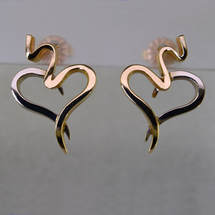 These distinguished heart earrings are the perfect earring for day or night. Stylish and modern, every girl will fall in love everytime she puts them on. Hand crafted in 14 karat yellow and white gold, you can wear these earrings with any outfit. Measures 3/4 inch long.   Designed, and created in our studio by the artist Stuart J.