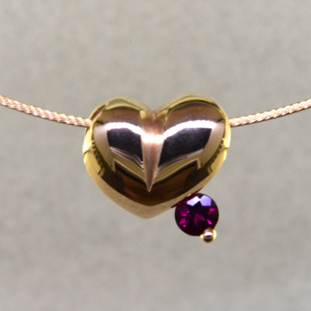 This lovely puffed heart pendant will make you feel happy every day. The ultimate fun heart with a deep red round rubellite tourmaline. This 14 karat yellow gold heart measures 1/4 inch long, and hangs on a 14 karat yellow gold 1mm wire, 16 inches long.   Designed, and created in our studio by the artist Stuart J.