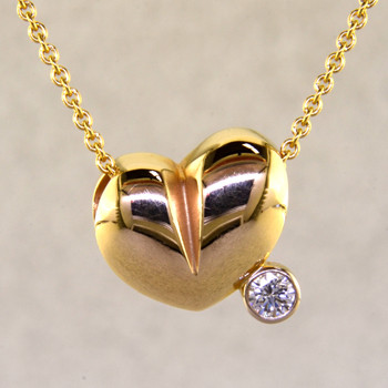 This lovely puffed heart pendant will make you feel happy every day. The ultimate fun heart with a .10ct. sparkling diamond. This 14 karat yellow gold heart measures 1/4 inch long, and hangs on a 14 karat yellow gold 1mm cable chain, 18 inches long.   Designed, and created in our studio by the artist Stuart J.