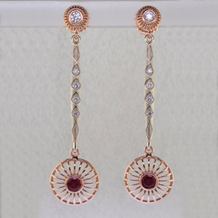 You will look spectacular and feel like a princess in these regal, sophisticated diamond and ruby earrings that dangle and dance. Hand crafted in beautiful 14 karat rose and white gold. At the top are two beautiful 1/5 carat ideal cut diamonds, with another .28ct of ideal cut diamonds sprinkled in the white gold bars, for a total of .68ct. Dangling on the bottom are interchangeable rose gold drops that each hold a beautiful 5mm Chatham® created rich red ruby. We can make the bottoms with any gemstone you like, to match any outfit in your wardrobe. These earrings measure 2 1/2 inches long and are designed and handcrafted by the artist Stuart J. Call us for more information about how we can customize this design Just For You.  Chatham® Created Gemstones are grown in carefully controlled laboratory conditions. They are chemically and optically identical to their natural counterparts, yet cost much less. Because the environment in which they are grown is controlled, the imperfections often found in natural gemstones, are absent in Chatham® Created Gemstones. Because of this, and superior cutting, Chatham® gems exhibit the color and sparkle of the finest natural gems. Eco-friendly and conflict free, each one comes with a Certificate of Authenticity, and a Lifetime Warranty.