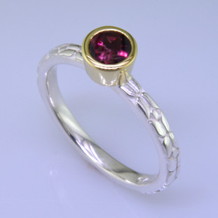 This cool, hip, and fun stackable ring is the start of your new collection. This ring will have many different looks when you stack it with other rings, or enjoy it alone in your everyday style. Hand finished in Sterling sliver with an 18 karat yellow gold bezel holding a beautiful .65ct.round rhodolite garnet. Finger size 7. We will make this in any size you need in about ten days.  Designed, and created in our studio by the artist Stuart J.  This ring is also shown in other gemstone colors and sizes, which are sold separately, and can be stacked with all other rings in our stackables collection. You can also stack it with any ring you like. There are no rules. Call us with your favorite color, and we will customize this Just For You.