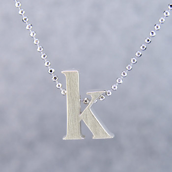 """What's your story? Begin with this Little """"K"""" initial solid Sterling Silver pendant. Wear it alone, with other pendants, or layered with other necklaces. Comes with a sterling silver ball chain, 16 inches long. The pendant measures 1/4 inch long. Too cute!  Signified by a feminine sensibility and optimistic charm, Alex Woo's Little Icon Collections reinvent familiar symbols from the world around us into fresh and expressive designs.  Designed and handcrafted in our studio."""