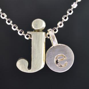 "What's your story? Begin with this Little ""J"" initial solid Sterling Silver charm. Wear it alone, with other charms (such as the Mini ""e"" shown, and sold separately), or layered with other necklaces. Comes with a sterling silver ball chain, 16 inches long. The charm measures 1/4 inch long. Too cute!  Signified by a feminine sensibility and optimistic charm, Alex Woo's Little Icon Collections reinvent familiar symbols from the world around us into fresh and expressive designs.  Designed and handcrafted by Alex Woo in New York City."