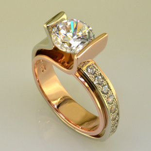 You will make a statement wearing this contemporary diamond engagement ring. Elegant flowing lines and contrasting metals make this design both modern and timeless. Shown in 14 karat white and rose gold, with 0.30ct. of round brilliant ideal cut diamonds, and a 1.50ct. center diamond (priced separately or we can use your diamond). We are happy to customize this special engagement ring any way you like, including using different metals like 18k yellow gold and platinum, and using your diamonds.  This custom designed diamond engagement ring is individually crafted, to be Perfectly You, and takes about 3-5 weeks to create. Call us for more information about how we can customize this design Just For You. Designed, and created in our studio by the artist Stuart J.