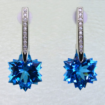 What's better than one sparkling snowflake? Two, of course. One for each ear. And you can turn up the heat, because these snowflakes won't melt. Exclusively ours, each blue topaz snowflake is custom cut just for us, in Canada, by master gem cutters who know what snowflakes look like. Each snowflake measures 12mm, and dangles from the bottom of 14 karat white gold icicle Piercettes®, glistening with .16ct. T.W. of ideal cut diamonds. These gorgeous earrings measure 1 inch long, and have posts with clutch backs. They are available with Colorless Topaz, Amethyst, and Citrine.  Other colors could take up to 8 weeks delivery, but ask anyway!  Designed and handmade by the artist Stuart J.  A Piercette® is a patented method of setting, with a gemstone that moves. The gem is set so that it swivels with every movement of the wearer, exhibiting extra sparkle.