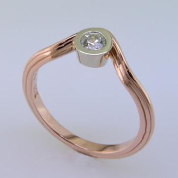 If you like unique, this rose gold diamond ring is for you. Clean simple lines make this ring feel light and modern. The beautiful .20ct. center diamond is floating in a 14karat white gold bezel. Wear it as a diamond engagement ring, or a fun pinky ring. Add our Dani Rose diamond eternity wedding band to complete the look. Call for details on how we can make it custom designed for you. Finger size 6 3/4.    Custom made by the artist Stuart J.