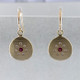 These sweet earrings shimmer when you wear them. Beautiful and rich 18 karat yellow gold medallion drops sprinkled with .11ct. of ideal cut diamonds set in a starburst pattern, with a glowing ruby in the center, hanging from wires. 12mm long.    Designed and created in our studio by the artist Stuart J.