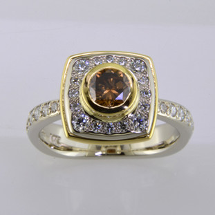 Here is a diamond halo engagement ring with a sophisticated flare. Custom designed with .45. T.W. of pavé set ideal cut diamonds makes this ring sparkle like crazy! A beautiful .57ct. round natural cognac color diamond is the focal point of this uniquely styled pavé halo diamond ring. It is set in an 18 karat yellow gold bezel to accentuate its vivid color, and also happens to make it look more like a one carat diamond! And not a single prong to worry about! This pavé diamond engagement ring feels smooth and is easy to wear. It is hand made in 14 karat white gold, with an 18 karat yellow gold border to beautifully frame the diamond halo. You will love the custom touches on this sweet engagement ring, like the beautiful open design on the underside.  As with all of our designs, we will make this any way you like, with any gemstones you like.  Custom designed and hand crafted in our studio by the artist Stuart J.