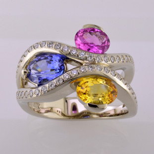 You will feel special with this very special gemstone ring on your finger. This unique, custom designed diamond and natural color sapphire ring has a display of color to rival nature! Yummy Blue, Yellow, and Pink oval, natural color sapphires, intertwined with .45 carat total weight of sparkling ideal cut diamonds. All meticulously set in 14 karat white gold. This diamond and sapphire gemstone ring will warm your heart, and make you smile every day! :) The finger size is 7, and can be sized up or down about 2 two sizes, plus or minus.  This is a special, one of a kind piece.  Designed and created in our studio by the artist Stuart J.