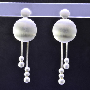 Fun, and funky earrings for the adventurous girl. Sterling silver dangles with round shapes, dangling on wires accented with small round silver beads, resting on posts. You will love these earrings! Measures 1 3/4 inch long, and handmade in Istanbul.