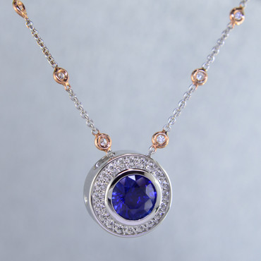 """Modern and timeless blue sapphire halo pendant, thoughtfully crafted in recycled 14 karat white gold will light up the room! Set with .29 carat total weight of super sparkly Ideal cut diamonds, and an incredible 2.87 carats natural Ceylon blue sapphire gemstone. This sapphire and diamond pendant has no prongs to worry about, and can be dressed up or down to go with any outfit. Dress it up with the included 14 karat white gold diamond station chain with rose gold accents, with a third carat of diamonds, measuring 18"""" long. A truly spectacular piece, that will never be out of style!  Designed, and created in our studio by the artist Stuart J."""
