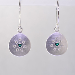 These sweet earrings have a special, hand applied finish that shimmers when you wear it. Beautiful and rich tarnish free sterling silver, sprinkled with .11 carat total weight of ideal cut diamonds, with glowing chatham created emerald gemstones(2mm) in the center. Dangles on sterling silver wires and measures 1 inch long. Available in other colors.  Please call for pricing.   Designed and created in our studio by the artist Stuart J.  Chatham Gemstones are also available in Ruby, Sapphire, and Alexandrite.                                                                                                                                                                                                                                                                                                                                                                                    Chatham® Created Gemstones are grown in carefully controlled laboratory conditions. They are chemically and optically identical to their natural counterparts, yet cost much less. Because the environment in which they are grown is controlled, the imperfections often found in natural gemstones, are absent in Chatham® Created Gemstones. Because of this, and superior cutting, Chatham® gems exhibit the color and sparkle of the finest natural gems. Each one comes with a Certificate of Authenticity, and a Lifetime Warranty.