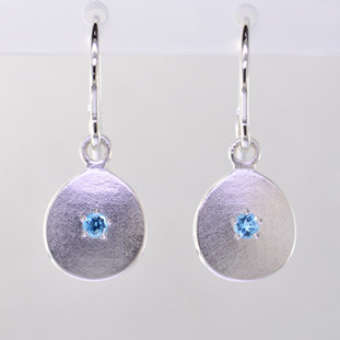These sweet gemstone earrings shimmer when you wear them. Beautiful in Sterling silver, these medallions with bright blue topaz gemstones in the center, hanging from sterling silver wires.  Earrings measure 3/4 inch long. Available in other colors. Please call for pricing.  Designed and created in our studio by the artist Stuart J.