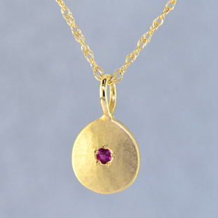 This sweet gemstone pendant shimmers as you wear it. Beautiful in 14 Karat yellow gold, this medallion has a rich deep red ruby gemstone in the center, and hangs on a 1 mm 14 karat yellow gold rope chain,18 inches long.Pendant measures 3/4 inch long. Available in other colors. Please call for pricing.  Designed & Created in our studio by the artist Stuart J.