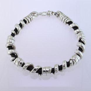 Edgy and modern, this leather and sterling silver man's bracelet makes a statement in a classy, understated way. The genuine leather runs through the center, with solid sterling silver coils on top, and a sturdy clasp. Will fit an 8 inch wrist, and can be sized down only.  by David Heston of San Rafael, California.