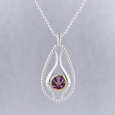 """You will be captivated by this mix of modern and vintage in this elegant pendant.  The mix of sterling silver and 18K green gold is magical as this pendant comes together. The 18K bezel make this 8mm rhodolite garnet stratus gemstone pop as it is smooth and has a beautiful deep reddish color.The blend of the two metals is sophisticated, and fun, all at the same time. Perfect for any time of the day or night. This pendant hangs on a sterling silver bead chain, 20"""" long. The pendant measures 1 3/4 inches long.  Designed, and created in our studio by the artist Stuart J."""