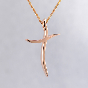 Elegant and modern, 14 karat rose gold curvy cross pendant, hanging from a 1mm, 14 karat rose gold diamond cut rope chain, 16 inches long. Cross measures 1 1/8 inches long, by 3/4 inches wide.  Designed and created in our studio by the artist Stuart J.