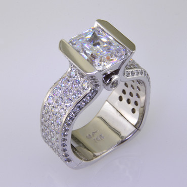 With this spectacular engagement ring on your finger, you will feel like royalty, and be the envy of all of your friends. With over 2 carats of Ideal cut diamonds, Sparkle is this rings middle name. There are no prongs to catch, and it is very comfortable to wear. Made for a 2.5 carat center diamond or gemstone (sold seperately), this custom designed engagement ring is individually crafted to be Perfectly You, and takes about 3-5 weeks to create. Call us for more information about how we can customize this design Just For You.Designed, and created in our studio by the artist Stuart J.  This diamond engagement ring is priced in 14k gold, and can be made in any karat or color, and in platinum. Makes a great anniversary gift for 20, 30 or more years together.