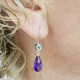"""We picked these beautiful Amethyst drops from Zambia because the color was so rich!  We added these beautiful light Blue Topaz for a perfect match.  Created in 14 Karat white gold, with these beautiful blue topaz buff tops set in bezels, and the amazing deep purple amethysts drops making these earrings the perfect accessory to any outfit!  These drop dangle earrings measure 1 1/4"""" long, and hang on 14 Karat white gold wires.  Designed, and created in our studio by the artist Stuart J."""