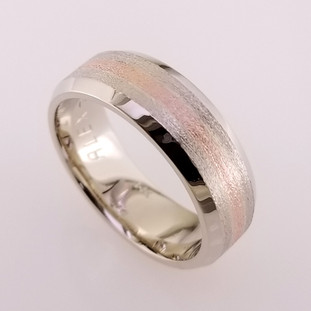 We custom make all our rings, so if you can think it, we can make it.  Here is a version of a simple and timeless man's wedding band that will last a lifetime.  We crafted it in 14 karat white gold 8mm wide, with a 2mm wide 14karat rose gold center. A perfect match to the brides halo engagement ring. Call us for more information about how we can make this design just for you, or keep it this way and enjoy it's beauty.  Designed, and created in our studio by the artist Stuart J.