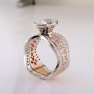 With this spectacular engagement ring on your finger, you will feel like royalty, and be the envy of all of your friends. With 1.08 carats of Ideal cut diamonds, Sparkle is this rings middle name. There are no prongs to catch, and it is very comfortable to wear. Made for a 2.5 carat center diamond or gemstone (sold separately), this custom designed engagement ring is individually crafted to be Perfectly You, and takes about 3-5 weeks to create. Matching diamond wedding band Ellie Di is also available. Call us for more information about how we can customize this design Just For You.Designed, and created in our studio by the artist Stuart J.  This diamond engagement ring is priced in 14k Rose gold, and can be made in any karat or color, and in platinum. Makes a great anniversary gift for 20, 30 or more years together.