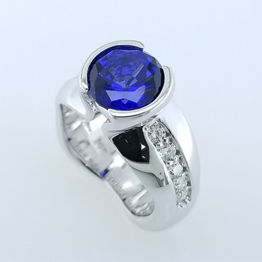 We like to make dreams come true.  We always love to make everything unique.  I think we accomplished this with this beautiful ring.  We created this sapphire and diamond ring in 14 Karat White gold, set .50ct. of ideal cut diamonds down the sides, and bezel set this amazing 3.17ct. Created round Blue Sapphire in the center.  All we can say is WOW!   This elegant ring is available in any karat or color of gold, and in platinum.  Designed, and created in our studio by the artist Stuart J.