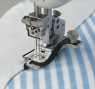 The Center Guide foot is used for lining up the center of a two or three needle stitch with a previously sewn seam. This attachment is especially useful on sportswear and allows you to tack down already sewn seams, give extra strength to seams that come under strain, or simply give a finished decorative effect.
