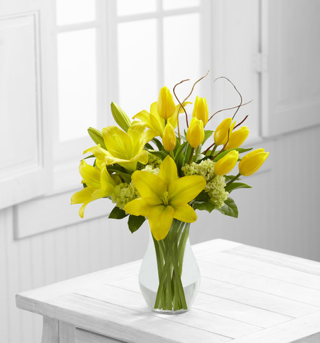 TheYour Day Bouquet is a bright and sunny display set to uplift their spirits with each exquisite bloom. Yellow tulips and Asiatic lilies are arranged amongst green mini hydrangea, lush greens and a curly willow accent. Seated in a classic clear glas