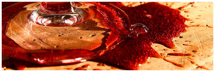 Glass stem with spilled perlé red wine on a table.