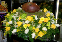 Football Player Casket Spray with football, yellow and white flowers with football placed on piece of grass.