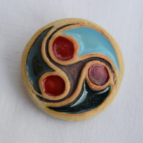 Triscele Brooch made from a white stoneware clay, coloured glazes and oxide. Piece comes displayed on a product card.