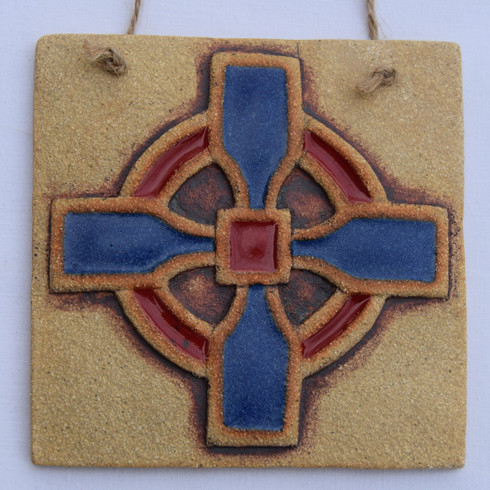 Cross plaque made from a textured stoneware clay, coloured glazes and oxide. Hessian string added to hang.