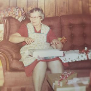 Grandma opening presents wearing a full apron during the holidays