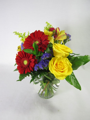 Red Gerbera Daisy, Bright yellow Roses in a compact vase.