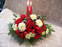 Double the light with this centerpiece. Full of winter greens and red and white flowers accented with pine cones and shinny red balls.