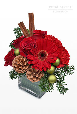 Red Gerbera, Red Roses, Cinnamon Sticks, Pine Cones, and shiney millimeter balls. With nice Vermont Winter Greens.