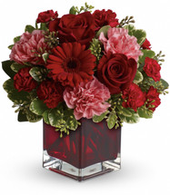mix of roses, carnations and more in shades of red and pink accented with greenery is delivered in a red glass cube vase.