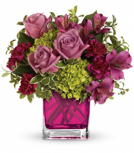 Green miniature hydrangea, lavender roses, purple alstroemeria and maroon miniature carnations accented with greens.